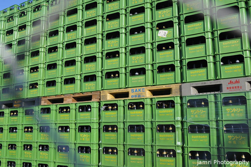 Through the fence.<br /> A lot of empty beer bottles ready to be refiled again at the nearby Suntory Brewery.