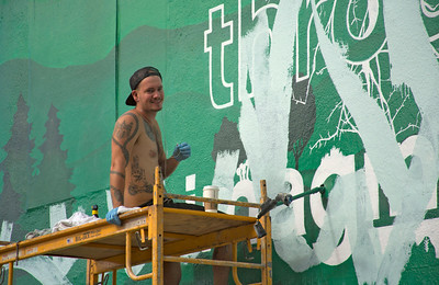 West Hollywood artist cleaning up grafitti from a wall mural.