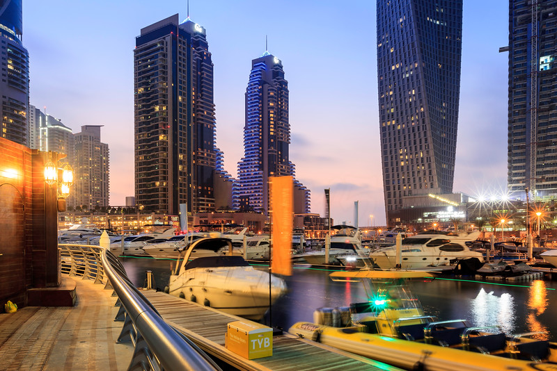 Blue hour shot of Dubai Marina with luxury boats and buildings.