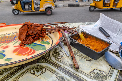 Fully cooked suya (sliced beef kebab on stick), with spice on a tray roadside Victoria Island Lagos Nigeria