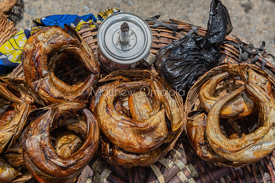 Street foods Lagos Nigeria, Close up Eja kika. Smoked rolled oily fish.  An oil lamp for night trading.