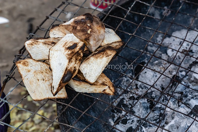 Street foods in Lagos Nigeria, Close up esun'su or roasted yam on charcoal fired grill by the roadside