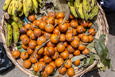 Agbalumo or African star apple and bananas on a tray/basket on Lagos street.
