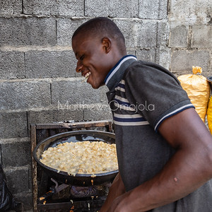 Street foods in Lagos Nigeria, Smiling happy Akara vendor. Akara (from ground beans) is frying in the Agbada (large round frying bowl)  usually in palm oil or soy oil. Using gas grill or stove.