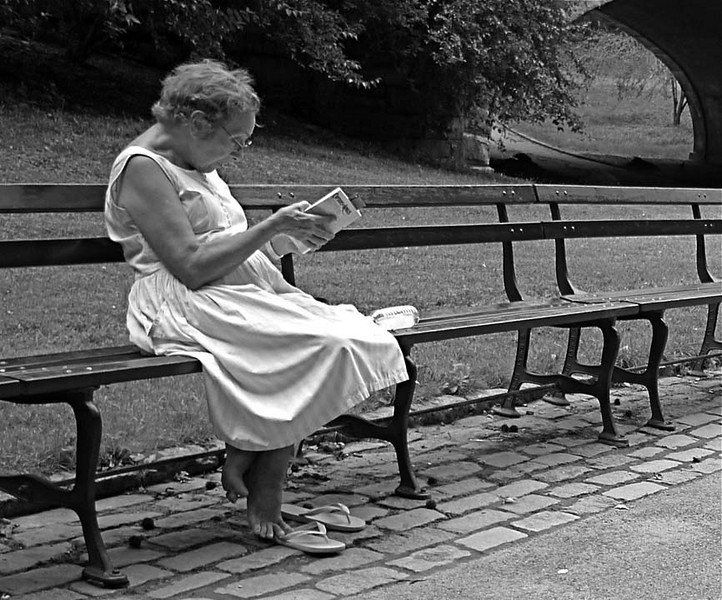 Summer reading<br /> <br /> I came upon this woman during a summer stroll through Central Park. She didn't look up to see me pass and take aim with my camera. Relaxed in her sun dress, rapt in her story, released from her feather-light footwear, she seemed about to ascend.