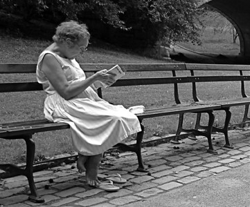 Summer reading  I came upon this woman during a summer stroll through Central Park. She didn't look up to see me pass and take aim with my camera. Relaxed in her sun dress, rapt in her story, released from her feather-light footwear, she seemed about to ascend.