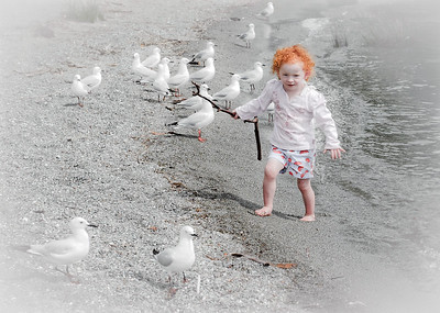 Red-headed little girl chasing seaguls, Te Anau, New Zealand