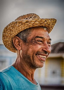 Cuba, Trinidad.  Portrait of a local cuban in straw hat with big smile.