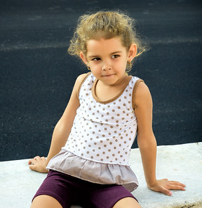 Cuba, Havana.  Young girl sitting on a wall on the Paseo del Prado,