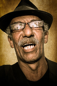 Cuba, Cienfuegos.  Portrait of a Cuban man with glasses and hat singing in the Jose Marti Square
