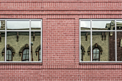 USA, Lafayette, Indiana. Brick building with reflections of historic Italianate buildings in windows.
