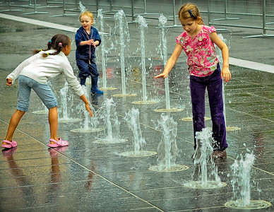 Montreal, Quebec, Canada.  Three young children playing in a street fountain getting wet.