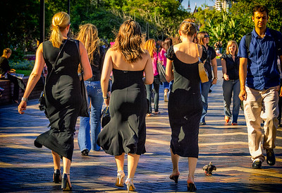 Australia, Sydney.  Three women in fancy black dresses and heels walking along crowded pathway in harbor area.