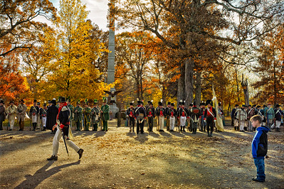 Battleground, Indiana.  Re-enactment of Battle of Tippecanoe with soldiers dressed in uniforms and carrying guns lined up for inspection and young boy spectator watching.