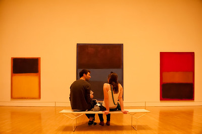 USA, Los Angeles, CA.  A young couple sitting on a bench in a museum talking and looking at paintings.