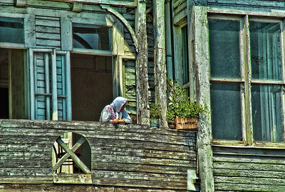 Istanbul, Turkey. Turkish woman on veranda, seen from a ferry trip on the Bosphorus