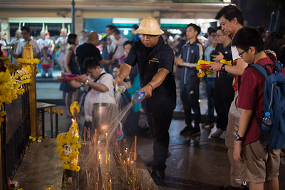 A shrine attendant extinguishes incense and prayer candles at Erawan Shrine in Bangkok, Thailand. December 10, 2017. Photo by Lorelei Trammell