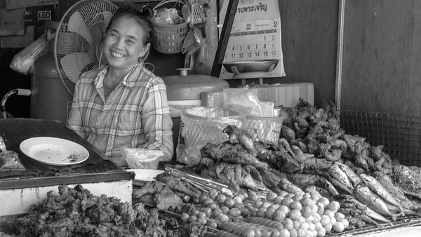 Smiling Thai woman working at food stall in local market in Chiang Mai