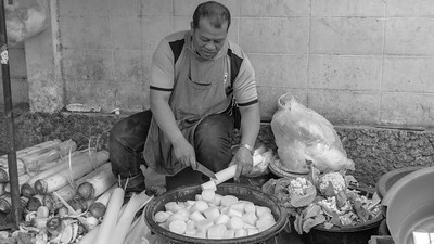 Thai man cutting fresh food at market in Chiang Mai