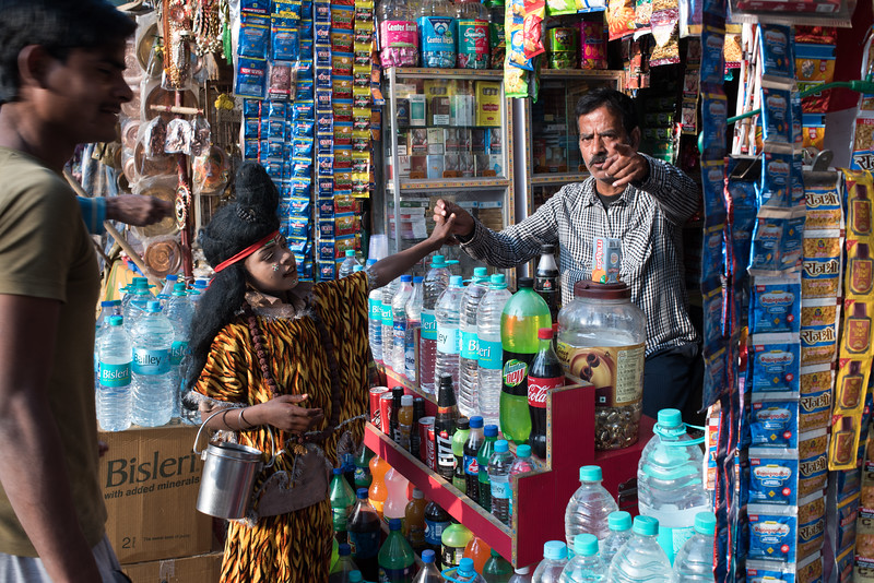 A boy dressed as Lord Shiva visits a general store in Varanasi, India. February 16, 2018. Photo by Lorelei Trammell