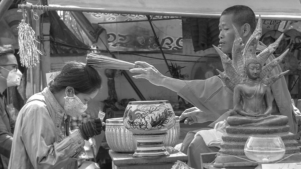 Monk bestowing a blessing on a Thai woman at the local market in Chiang Mai