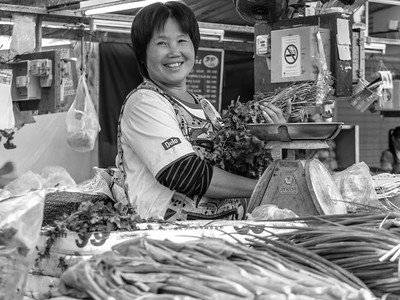Thai woman smiling while weighing vegetables at the local market in Chiang Mai