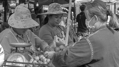 Two Thai women selling fresh fruit at the market in Chiang Mai
