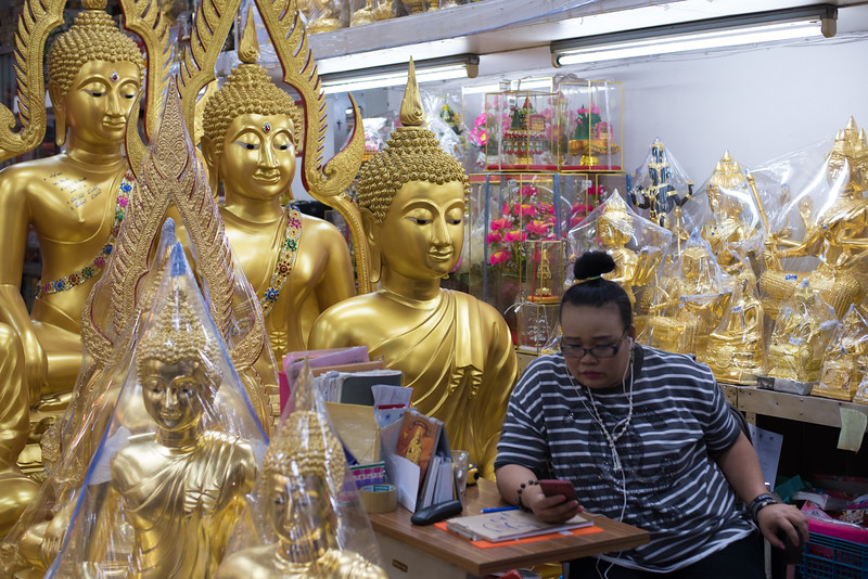 An employee at a store selling Buddha statues in Bangkok, Thailand. December 11, 2017. Photo by Lorelei Trammell.