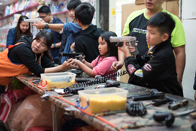 A woman teaches a girl how to use a bb gun at the Raohe Night Market in Taipei, Taiwan. November 9, 2017. Photo by Lorelei Trammell.