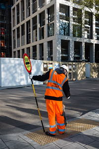 A building site workman on traffic management duty interacts with a squirrel he has made friends with. South Bank. London. April 18, 2017. Photo: Edmond Terakopian