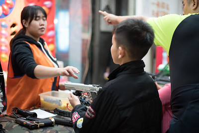 A game vendor reaches to take back a gun at Raohe Night Market in Taipei, Taiwan. November 9, 2017. Photo by Lorelei Trammell.