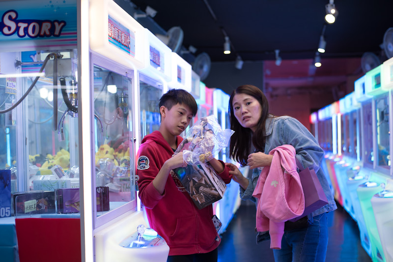 A boy unwraps the prize he won at the Tonghua Night Market in Taipei, Taiwan. November 11, 2017. Photo by Lorelei Trammell.