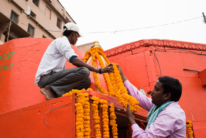 Men adorn a shrine with marigolds in Varanasi, India. February 13, 2018. Photo by Lorelei Trammell