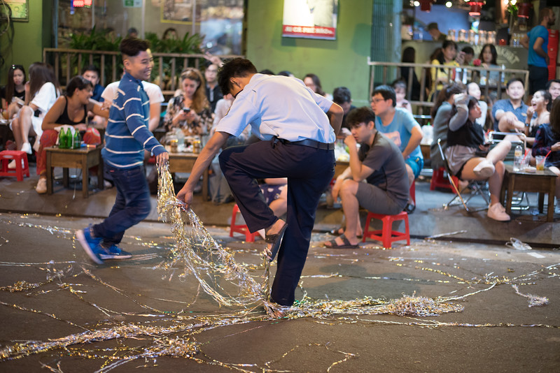 A boy assaults a security guard with streamers at Biu Vien Street in Ho Chi Minh City, Vietnam. January 13, 2018. Photo by Lorelei Trammell