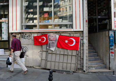 A man walks past national flags erected for Victory Day in Istanbul, Turkey. August 28, 2014. Photo by Lorelei Trammell
