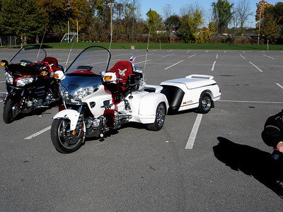 Cushy seat covers and a trailer.  So if I'm getting this right. The riders of the white Gold Wing travel in ultimate style on the road so they can stop in some farmer's field, downwind of the pig pen, and get back to nature.