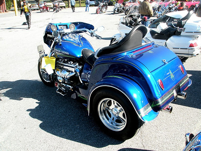 """So this guy, somewhere, obviously on a testosterone rush, sat down at his drawing board, and with his inebriated faculties thought to himself, """"What if I took the biggest motor Chevy makes and shoehorned it into a 900 pound motorcycle?""""  Further thinking came up with """"Wouldn't that be cool?""""  This blue Boss Hoss Trike is what he got.  One more wheel and it would be a convertible...but without the top."""