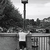 Lamprage. Jogger stretching out by Christianshavns Kanal, Copenhagen.