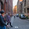 Flinders Lane with vehicles parked, people walking and crossing narrow city lane.