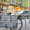 Religious sign on blackboard fixed to bicycle on city street with blurred vehicles passing in background.
