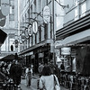 Grainy old-fashioned style image Degraves Street laneway with its, cafes, shops and characteristic signage as people walk through at start of day.
