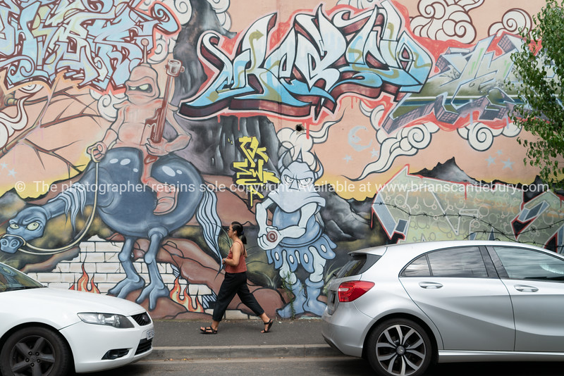 Woman walks on footpath between two cars and infront of street art on exterior wall.
