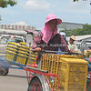 Bangkok, photograph of woman wheeling stack of produce baskets to maket. Thailand.