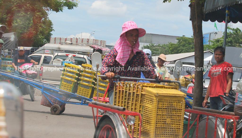 Bangkok, photograph of woman wheeling stack of produce baskets to maket. Thailand.