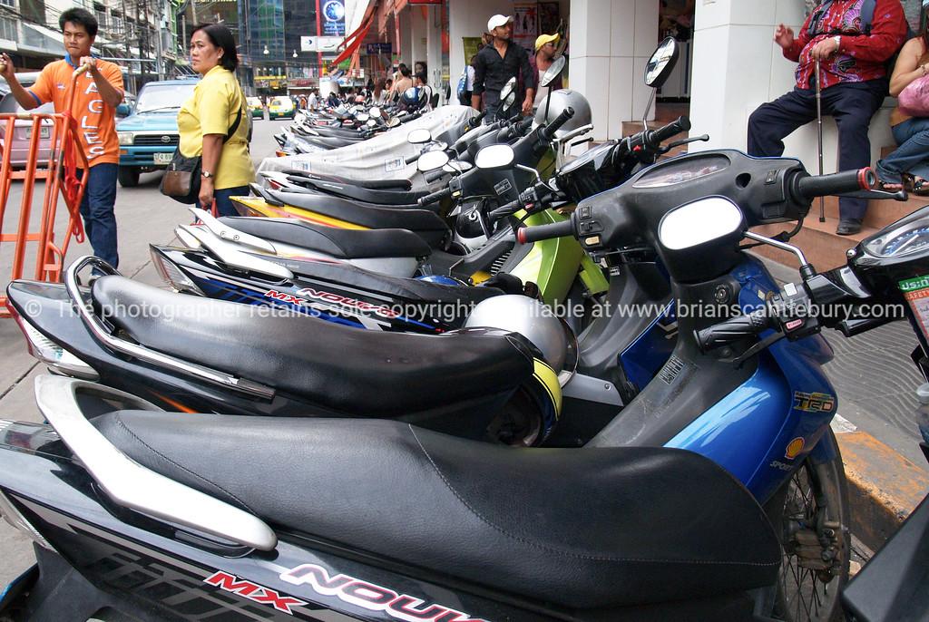 Bangkok street, row of parked motorcycles. Thailand.