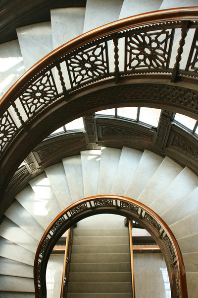 The Rookery's famous half round staircase leading down to the lobby.  The exterior walls of the staircase are lit by windows making the lighting just beautiful.