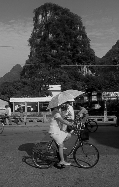 313  Yangshuo - Woman on a bike with parasol