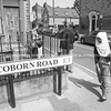 Woman in hajib walks around corner of Coborn Road past the road sign in monochrome.