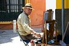 A painter sits in the street in Andalusia.  He doesn't seem to mind that I am taking his photo.  Not sure what feelings lurk beneath that look though.