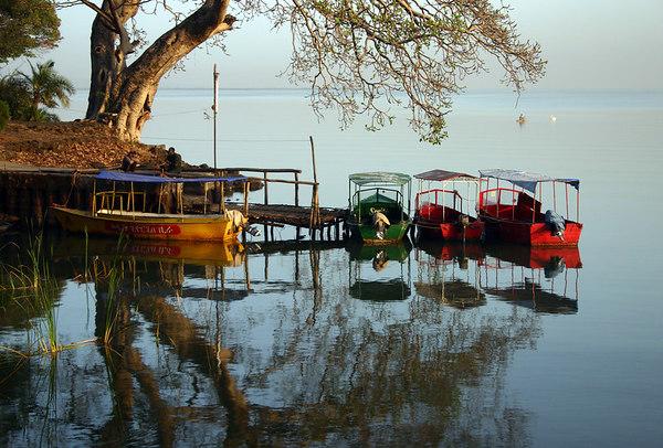boats docked on lake tana at the ghion hotel at dusk, bahir dar, ethiopia